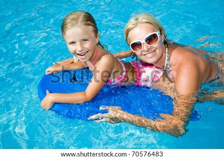 Little girl with mother boarding in blue water - stock photo