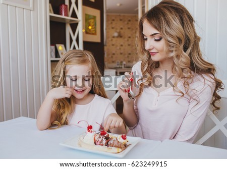 Little girl with mother eating ice cream in a cozy cafe.Good relationship of parents and child. Happy moments together.Beautiful family