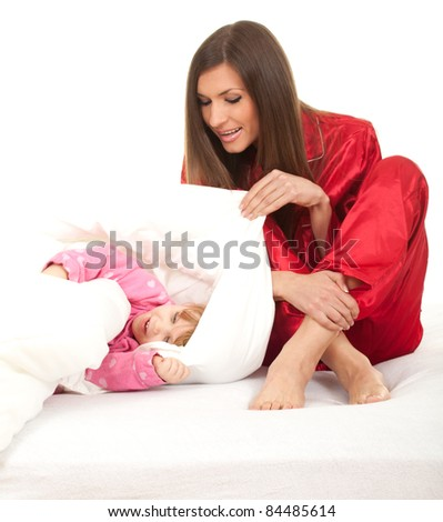 little girl with mother in white bedding - stock photo
