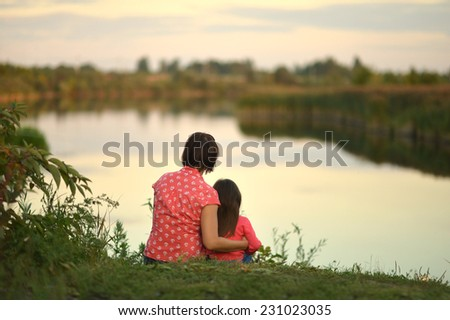 Little girl with mother near the lake,back view - stock photo