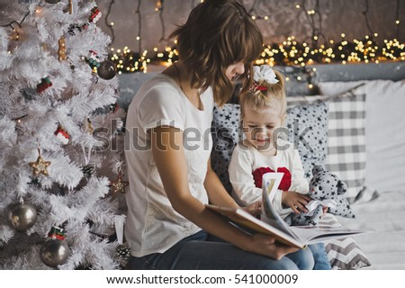 Little girl with mother reading a book sitting under the Christmas tree.