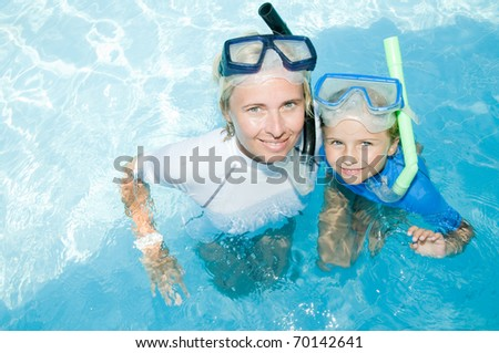 Little girl with mother snorkeling in blue water - stock photo