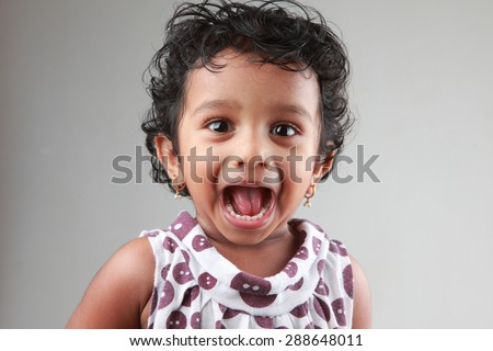 Little girl with mouth open shows her teeth - stock photo