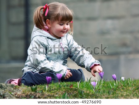 little girl with new spring flowers - stock photo