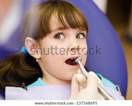 little girl  with open mouth during drilling treatment at the dentist - stock photo