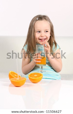 Little girl with oranges and juice on white sofa and background. - stock photo