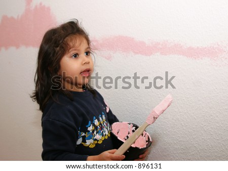 little girl with paint brush painting her room