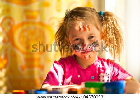 Little girl with paint of face. - stock photo