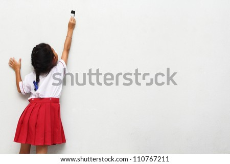 little girl with paintbrush on wall, back view - stock photo