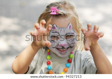Little girl with painted face as a cat - stock photo