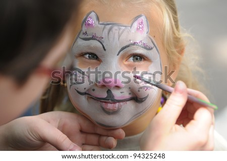 Little girl with painting face as a cat - stock photo