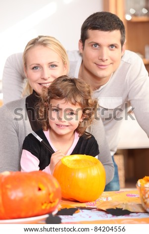 Little girl with parents preparing pumpkin for Halloween - stock photo