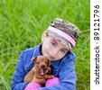 little girl with pet puppy mascot mini pincher in outdoor green grass - stock photo
