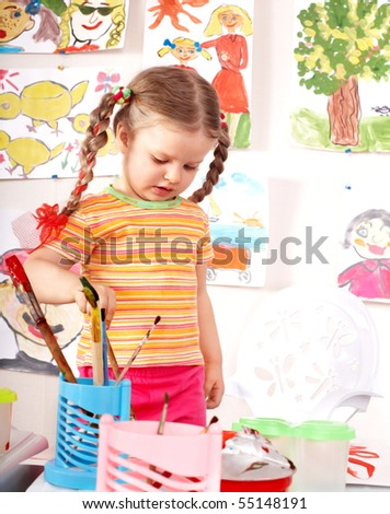 Little girl with picture and brush in playroom.
