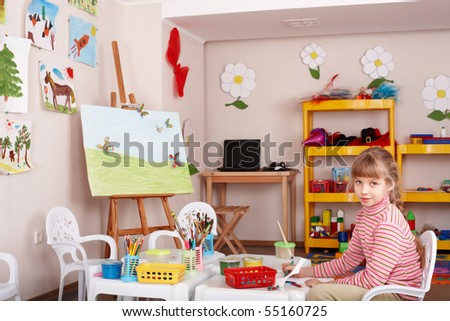 Little girl with picture and brush in playroom. - stock photo