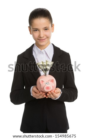 Little girl with piggy bank. Cheerful little girl in formalwear holding piggy bank and pointing it while standing isolated on white - stock photo