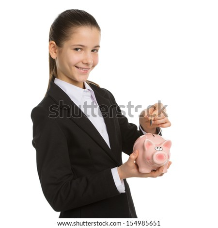 Little girl with piggy bank. Smiling little girl in formalwear holding piggy bank and putting coins in it while standing isolated on white - stock photo