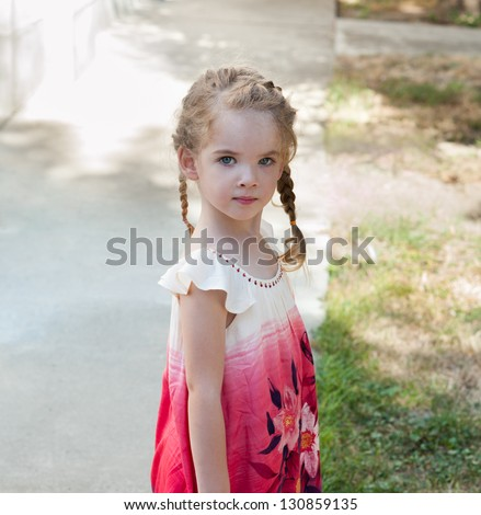 little girl with pigtails in a red dress - stock photo