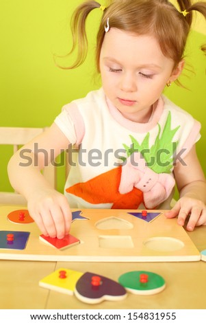 Little girl with pigtails puts wooden geometric shapes on the board - stock photo