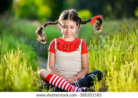 Little girl with pigtails shows the language - stock photo
