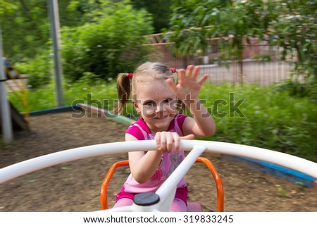 little girl with pigtails spinning on the carousel
