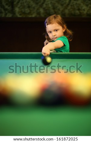 Little girl with pigtails starts the game of pool in the billiards hall