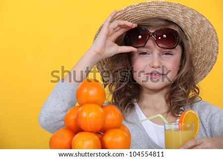 Little girl with pile of oranges wearing straw hat - stock photo