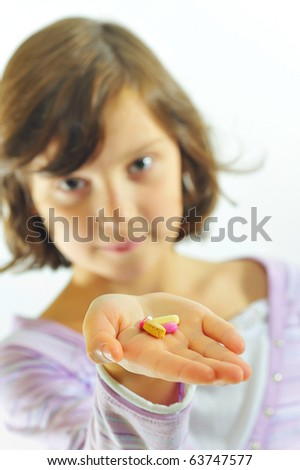 little girl  with pills in hand - stock photo