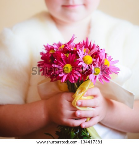 Little girl with pink flowers asters in their hands - stock photo