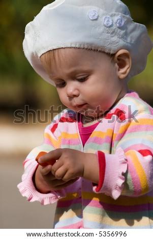 Little girl with plastic bottle cap in her hands. - stock photo