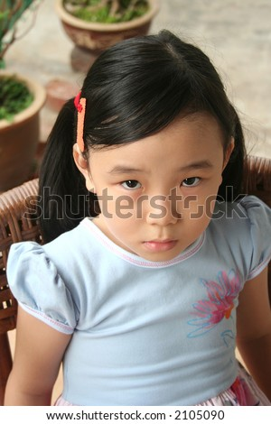 Little girl with pony-tail sitting on a rattan chair with unhappy expression - stock photo