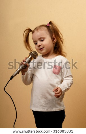 Little girl with pony tails holding microphone and singing, vertical indoor shot - stock photo
