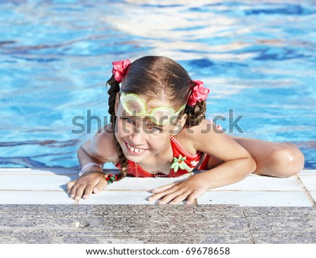 Little girl with protective goggles and red swimsuit in swimming pool.