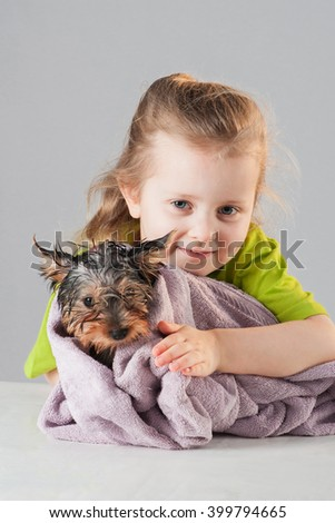 Little girl with puppy after his bath