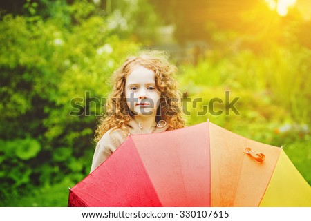 Little girl with rainbow umbrella, under sunshine. After the rain. Protecting healthy life and happy childhood concept. - stock photo