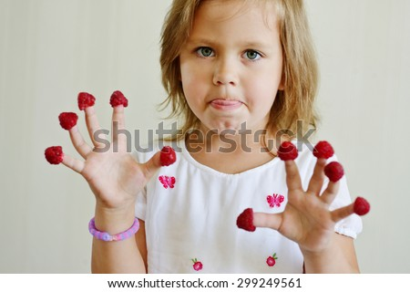 little girl with raspberry on her fingers - stock photo