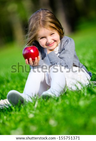Little girl with red apple sitting on the grass in the summer park - stock photo
