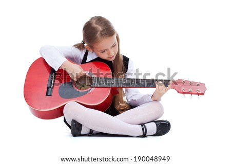Little girl with red guitar sitting on the floor - isolated - stock photo