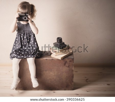 little girl with retro camera on suitcase indoor - stock photo