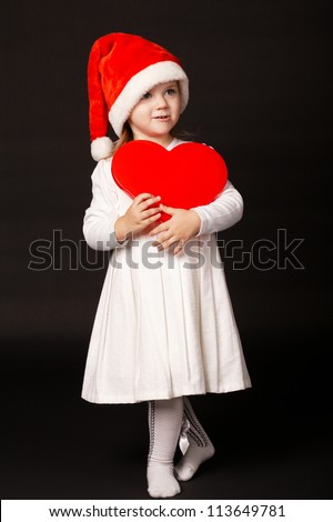 little girl with santa hat holding heart - stock photo