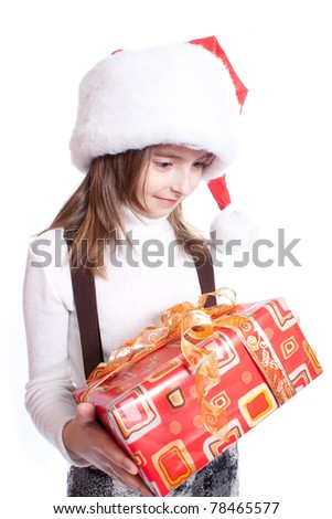 Little girl with santa's hat and gift holding - stock photo