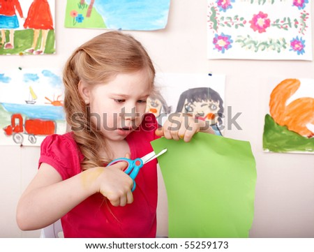 Little girl  with scissors cut paper at home. - stock photo