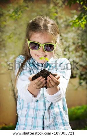 Little girl with seedling - stock photo