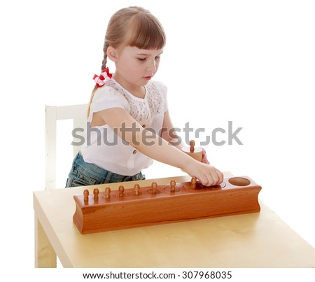 little girl with short bangs and thin hair on his head sitting at a table in a Montessori kindergarten. A girl student of mathematics-Isolated on white background - stock photo