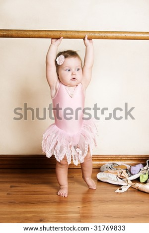 Little girl with short hair wearing a pink ballet outfit - stock photo