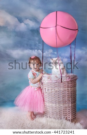 Little girl with siberian cat in basket of balloon  on blue sky background - stock photo
