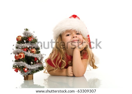 Little girl with small christmas tree on the table dreaming about the holidays - isolated, copy space - stock photo