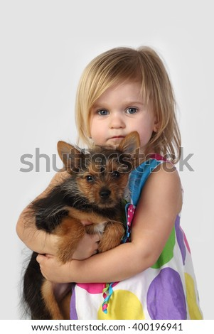 Little girl with small dog in hands on gray background
