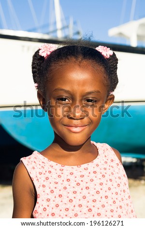 little girl with smiling eyes and boat - stock photo
