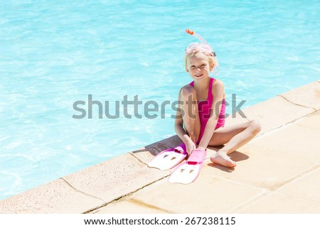 little girl with snorkeling equipment at swimming pool - stock photo